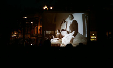 Katherine Vernez, Siddiqua Akhtar and Ros Philips reenact Mary Wollstonecraft. They were filmed speaking from her pew in the Unitarian Chapel, Newington Green, Hackney, and then projected onto Newington Green as a part of the outdoor screening and picnic event in 2007