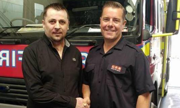 Constantin Huber (left) shakes hands with a fire fighter during a visit to Homerton Fire Station. Photgraph: London Fire Brigade
