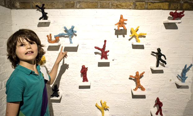 A young artist stands beside the 'oil and wire figures dipped in acrylic paint'
